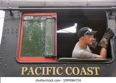 Cass, West Virginia/USA- May 26, 2018: A horizontal closeup image of a steam train engineer driving the train into the station to pick up passengers.