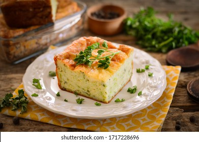 Casserole with cheese and herbs. A piece of casserole on a plate