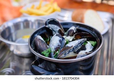 Casserole with cooked black mussels in a creamy sauce. Obes from seafood. Focusing on mussels. - Shutterstock ID 1813704304