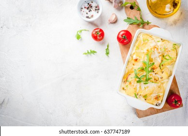 Casserole. French cuisine. Homemade potato gratin in a ceramic frying pan for baking. On a white marble stone background. With leaves of fresh arugula, tomatoes, olive oil. Top view copy space