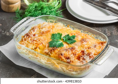 Casserole with potatoes, melted cheese, fresh green apple and lemon