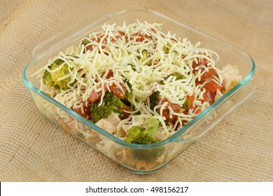 Casserole preparation with pasta, canned chicken chunks and steamed broccoli with marinara sauce and shredded cheese.