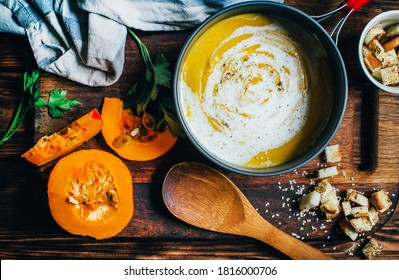 casserole with pumpkin soup next to pumpkin croutons with greens a wooden spoon on a dark brown wooden table close-up top view