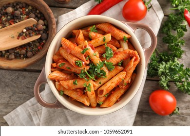 Casserole of tasty penne pasta with tomato sauce on wooden table, top view