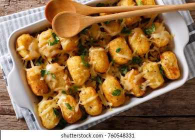 Casserole of Tater Tots with cheese and herbs close up in a baking dish on the table. horizontal top view from above