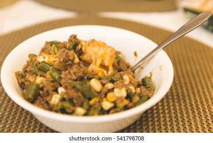 Casserole in a white bowl with hamburger, green beans, tater tots, and corn.