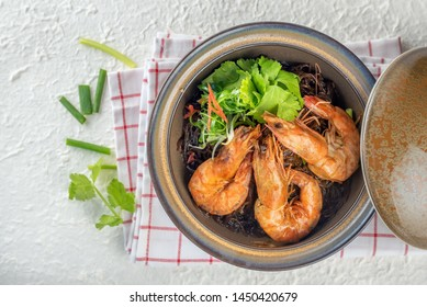 Casseroled prawns with vermicelli in brown clay pot or glass noodle bake with shrimp. Casseroled prawns in glass noodle is Chinese food make in Thai food style and can order at all Thai restaurant.