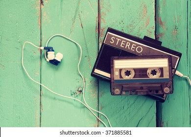 Cassette and old tape player over wooden background. retro filter
