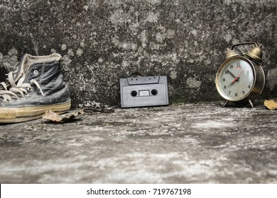 Cassette on concrete and old wall as a backdrop. Sneakers and old clock, old story featured a flashback to the 70s-90s.