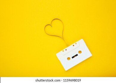 Cassette tape with heart shape on yellow background