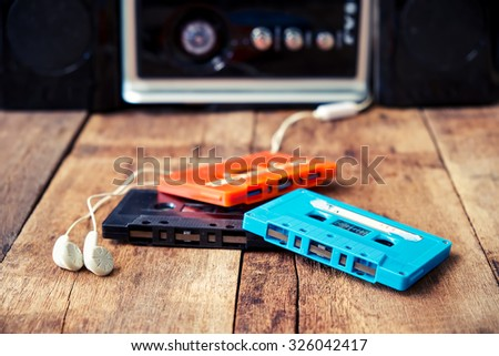 Cassette Tape Over And Earphone On Wooden Table Vintage Effect