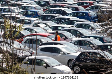 Cassino, Italy - March 22 2012: A worker checks newly-manufactured Fiat, Lancia and Alfa Romeo automobiles parked outside the Fiat SpA factory in Cassino, Italy.