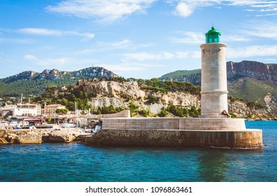 CASSIS, FRANCE - OCTOBER 10, 2009: Lighthouse on pier and Chateau de Cassis castle in background on bright sunny day in old port of Cassis