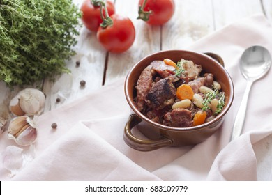 Cassoulet. Containing meat pork sausages, goose, duck and sometimes mutton and two types of white beans. French food. On old wooden white background.