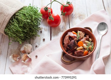 Cassoulet. Containing meat pork sausages, goose, duck and sometimes mutton and two types of white beans. French food (cuisine). On old wooden white background.