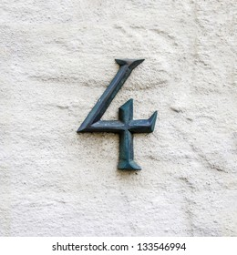 cast bronze house number four on a white plastered wall