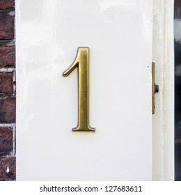 cast bronze house number one next to a door bell.