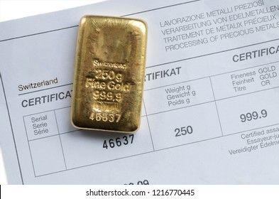 Cast gold bar weighing 250 grams on a background of a certificate.