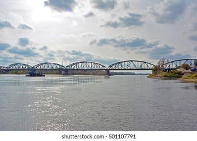 Cast iron arch bridge (truss bridge) over Vistula river, near the town of Bydgoszcz (Bromberg), with a passing barge