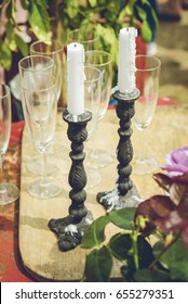 Cast iron candle sticks and champagne gasses. Garden party concept.