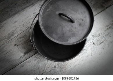 Cast Iron Dutch Oven Half Open On Wooden Background