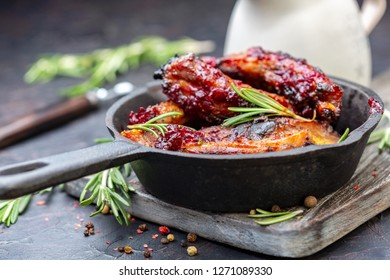Cast iron frying pan with baked honey pork ribs and rosemary on wooden serving board, jug with cherry sauce on textured dark background, selective focus.