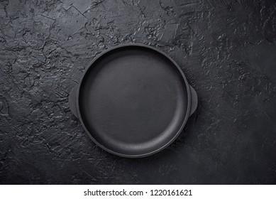 Cast iron frying pan on black slate backgound
