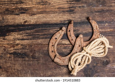 Cast iron metal horseshoes and rope. Good luck symbol, badly worn rusty horse accessories. Vintage wooden boards background, top view
