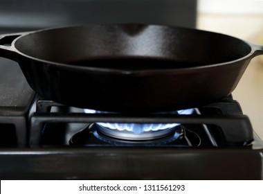Cast iron pan heating up on gas range stove.