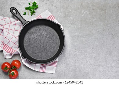 Cast iron pan on a grunge concrete background with copy space. Empty iron pan, top view or high angle shot with herbs and tomatoes.