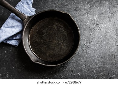 Cast iron pan on rustic black stone background close up -  empty black frying pan frying skillet with copy space