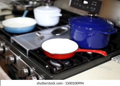 Cast iron porcelain enameled cookware on the stove top in a home kitchen.