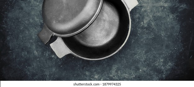 Cast Iron Pot With Cover Or Lid In The Form Of Separate Frying Pan. Top View. Casserole Pot On Black Shabby Background. Flat Lay. New And Clean Cast Iron Cookware.