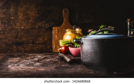 Cast iron pot with fresh herbs, spices and kitchen utensils for tasty cooking on rustic table. Healthy eating. Homemade cooking. Dark. Still life. Food background. Copy space