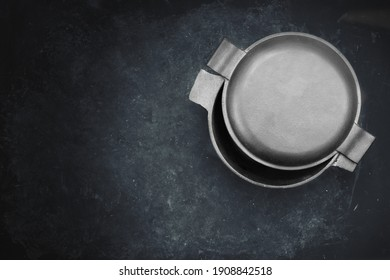 Cast Iron Pot With Half-Open Lid In The Form Of Frying Pan. Top View. Casserole Pot On Black Shabby Background. Flat Lay. New And Clean Cast Iron Cookware.