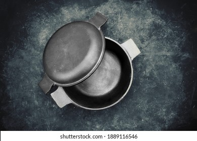 Cast Iron Pot With Lid In The Form Of Separate Frying Pan. Top View. Casserole Pot On Black Shabby Background. Flat Lay. New And Clean Cast Iron Cookware.