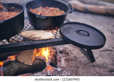 Cast iron pots of chilli sit atop an iron grill over a campfire