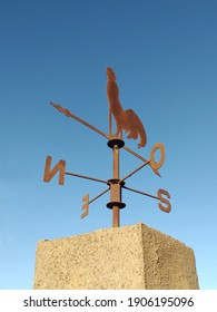 Cast iron rooster wind vane under blue sky. Weather vane to indicate the direction of the wind with a wrought iron rooster and cardinal points. Meteorology accessory concept.