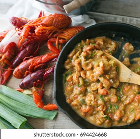 Cast iron skillet filled with crawfish étouffée being served. Top view.