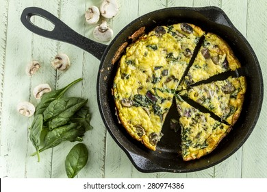 Cast iron skillet filled with a spinach mushroom and onion frittata with raw ingredients