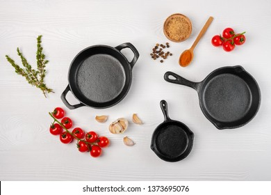 Cast iron skillets and spices on white wooden culinary background, view from above