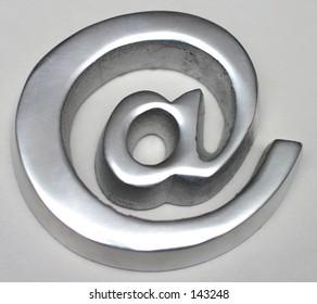 A cast metal '@' symbol