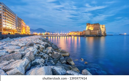 Castel dell Ovo (Egg castle) in Naples, Italy, view from the seaside quay in blue evening light