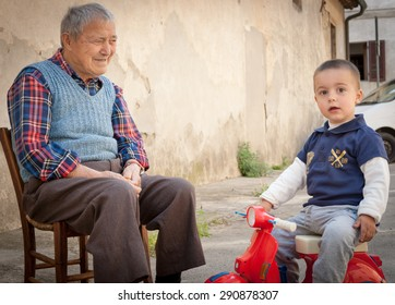 CASTEL SAN GIMIGNANO, ITALY- APRIL 21;Italian grandfather on old wooden chair in lane  caring for grandson looking towards camera on a red toy motor scooter  on April 21, 2011 in san Gimignano, Italy