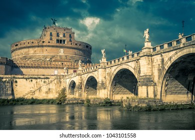 Castel Sant'Angelo in summer, Rome, Italy. Panorama of the old castle and bridge Ponte Sant'Angelo on the Tiber River in sunlight. Famous Sant'Angelo of the Renaissance against the dramatic sky.