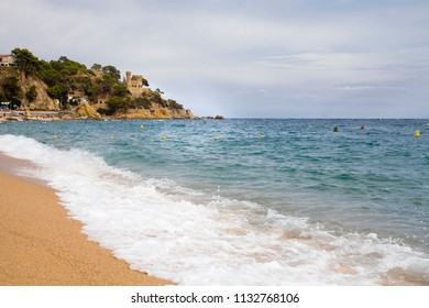 Castell d'en Plajan on the Costa Brava and city beach in Lloret de Mar, Spain. Sand and sea waves on Catalonia beach.