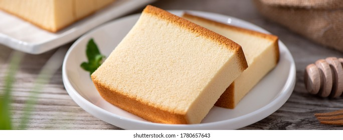Castella (kasutera) - Delicious Japanese sliced sponge cake food on white plate over rustic wooden table, close up, healthy eating, copy space design.