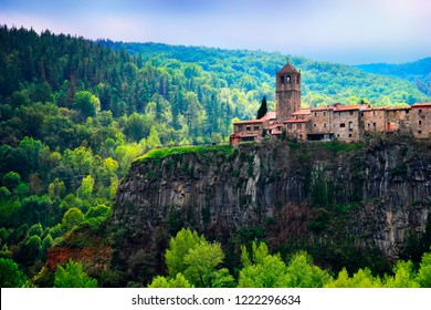 Castellfollit de la Roca, Garrotxa, Province of Girona, Catalonia, Spain, Europe. Beautiful scenic view, ancient church and town houses at the top of huge basalt cliff and green wood at the background