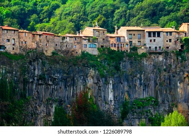 Castellfollit de la Roca, Garrotxa, Girona, Catalonia, Spain, Europe. Beautiful scenic view, ancient town houses over the huge basalt cliff and mountain covered with green wood at the background