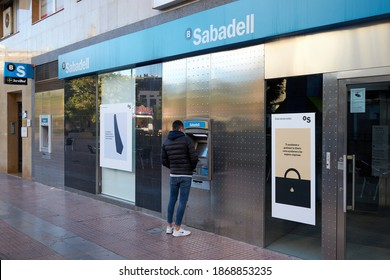 CASTELLON, NOVEMBER - 2020: A young man withdraws money from an ATM at Sabadell Bank